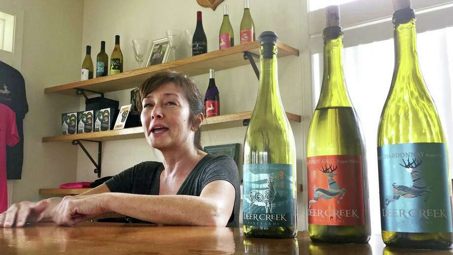 Vineyard owner Katherine Bryan laughs as she discusses the wines available for tasting at Deer Creek Vineyards in Selma, Ore. Bryan is one of a handful of vineyard owners and winemakers in this fertile corner of southwestern Oregon who are branching out into marijuana farming after the legalization of recreational weed in Oregon two years ago. Photo: Gillian Flaccus — The Associated Press  / Copyright 2017 The Associated Press. All rights reserved.