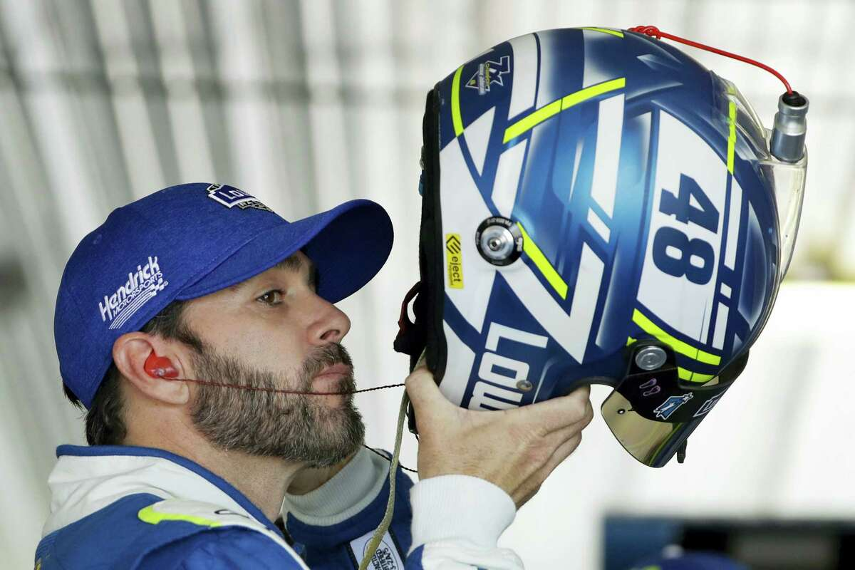 Driver Jimmie Johnson puts on his helmet before practice on Friday in Long Pond, Pa.