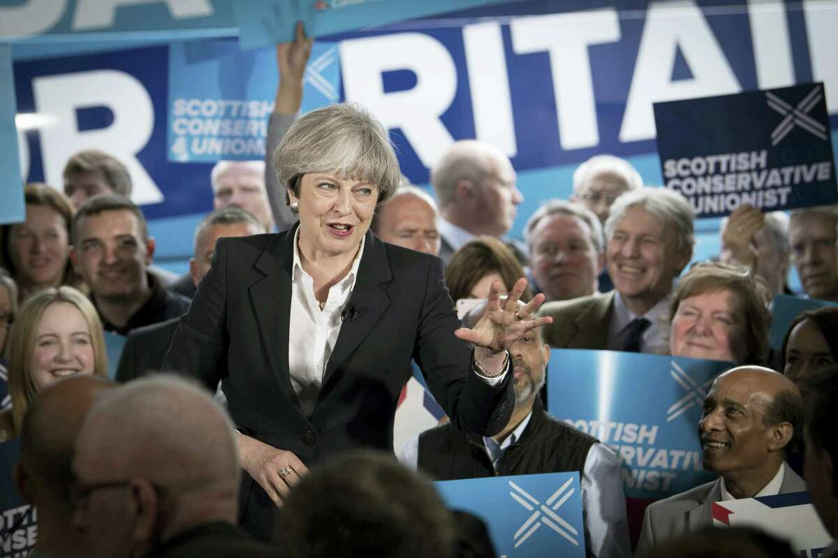 In this photo taken on Monday June 5, 2017, Britain's Prime Minister Theresa May speaks during a General Election campaign visit to Clockwork Removals and Storage in Edinburgh. Theresa May is often compared to Margaret Thatcher, depicted by supporters as a 21st-century Iron Lady. But a bruising election campaign has dented her steely reputation. Britain's 60-year-old prime minister called a snap election three years early in a bid to increase her party's slim majority in Parliament and strengthen her hand in divorce negotiations with the EU.
