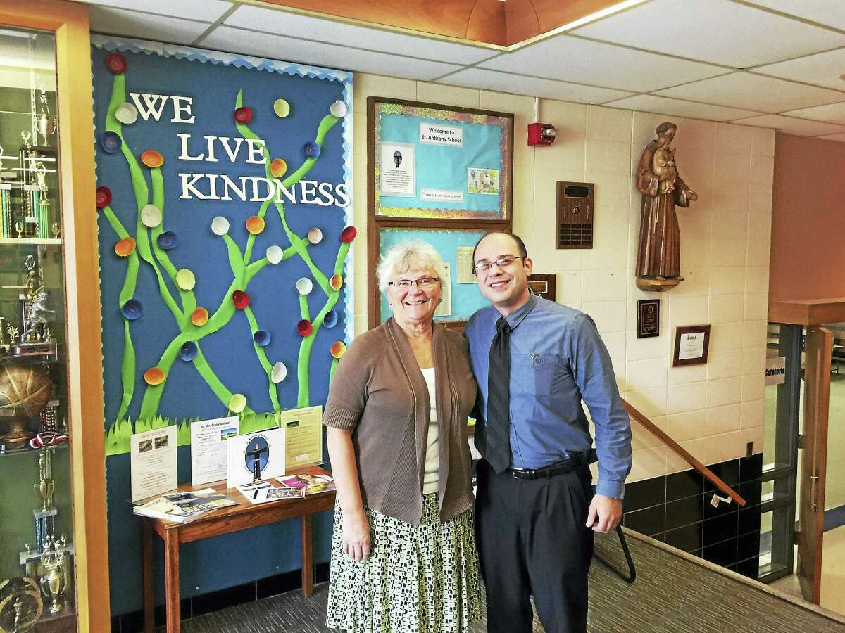 Retiring principal Patricia Devanney and new principal Lou Howe paused for a photograph on Friday in the halls of St. Anthony School in Winsted.