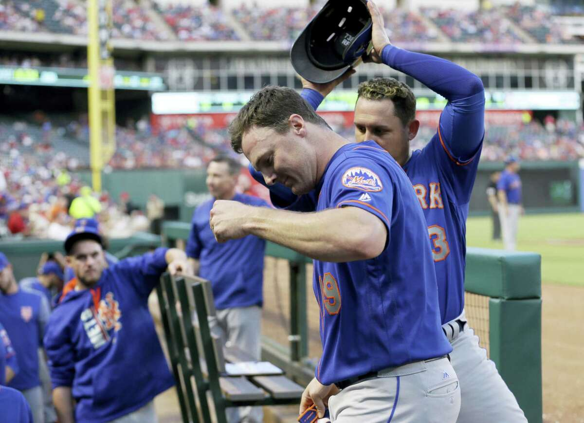New York Mets' Jay Bruce (19) has his helmet removed by Asdrubal Cabrera, rear, as they celebrate Bruce's two-run home run against the Texas Rangers during the fourth inning Wednesday in Arlington, Texas.