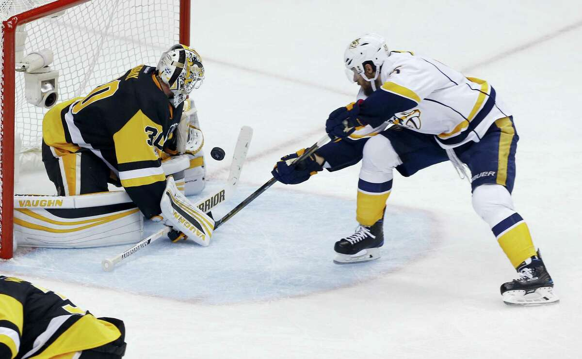 Pittsburgh Penguins goalie Matt Murray, left, stops a point-blank shot by Nashville Predators' Craig Smith during the third period in Game 5 of the NHL Stanley Cup Final Thursday in Pittsburgh. The Penguins won 6-0.
