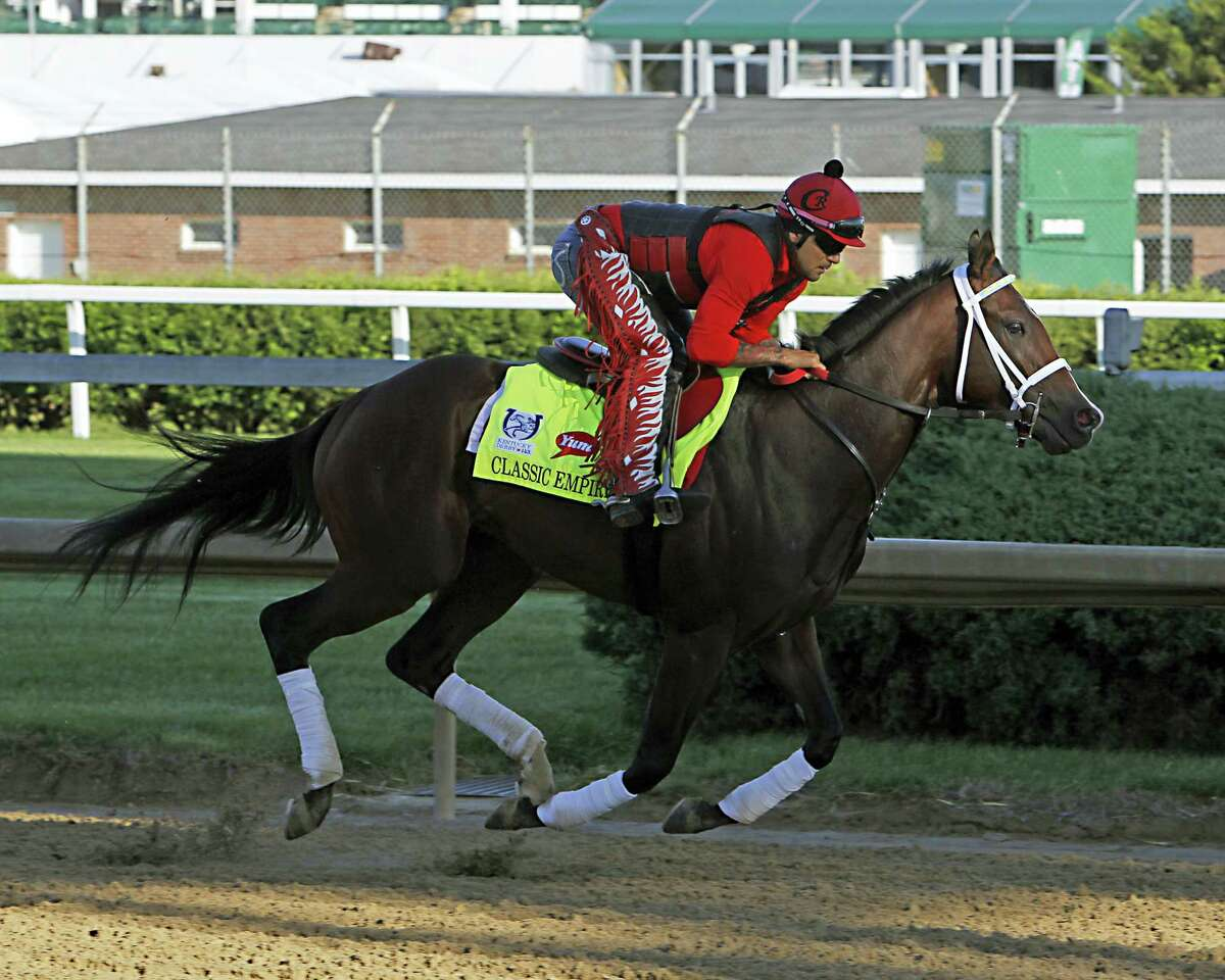 In this May 2, 2017 photo, Classic Empire exercise rider Martin Rivera up, gallops at Churchill Downs in Louisville, Ky. Classic Empire is out of the Belmont Stakes because of an abscess in his right front foot. Trainer Mark Casse says the abscess found June 7, 2017 is a recurrence of the same problem that bothered the colt after his loss in the Holy Bull in February. Classic Empire was expected to be the favorite for Saturday's 1½-mile finale of the Triple Crown series.
