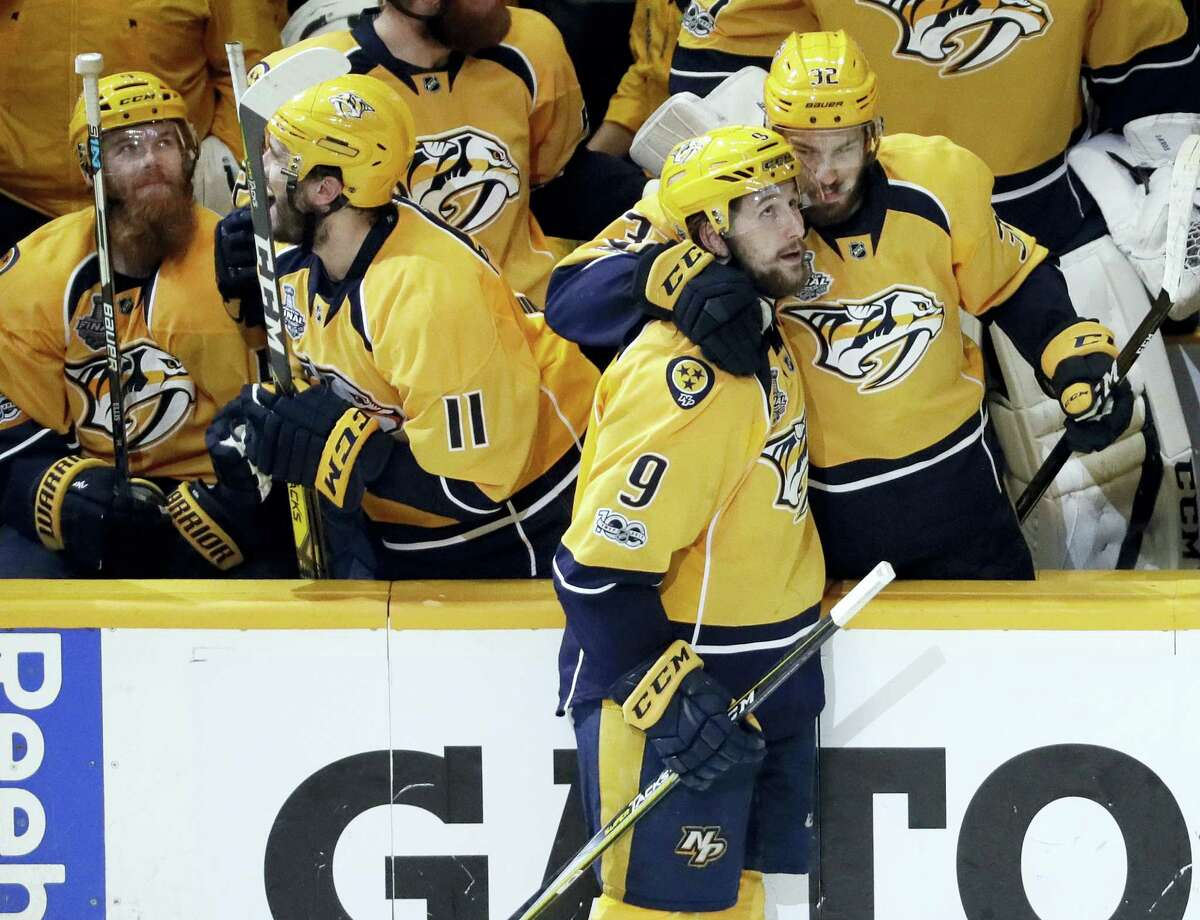 Nashville Predators left wing Filip Forsberg (9), of Sweden, is congratulated by Frederick Gaudreau (32) after Forsberg scored an empty net goal against the Pittsburgh Penguins during the third period in Game 4 Monday in Nashville, Tenn.