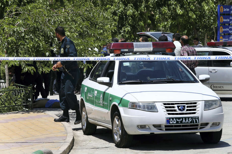 A body, background left, lies on the ground while police control the scene at the shine of late Iranian revolutionary founder Ayatollah Khomeini, just outside Tehran, Iran on June 7, 2017. Several attackers stormed into Iran's parliament and a suicide bomber targeted the shrine of Ayatollah Ruhollah Khomeini on Wednesday, killing a security guard and wounding 12 other people in rare twin attacks, with the shooting at the legislature still underway. Photo: AP Photo — Ebrahim Noroozi  / Copyright 2017 The Associated Press. All rights reserved.