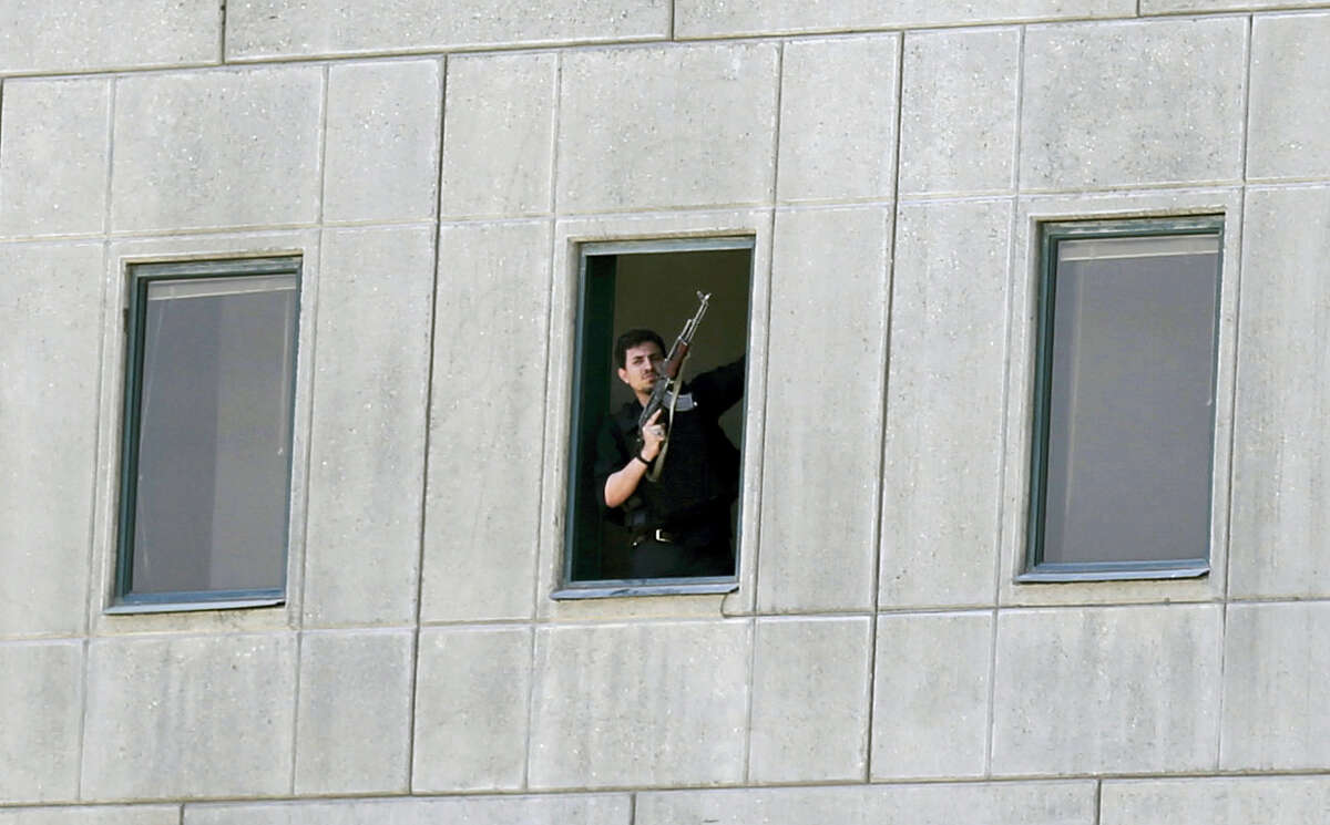 An armed man stands in a window of the parliament building in Tehran, Iran on June 7, 2017. Several attackers stormed into Iran's parliament and a suicide bomber targeted the shrine of Ayatollah Ruhollah Khomeini on Wednesday, killing a security guard and wounding several other people in rare twin attacks, with the shooting at the legislature still underway.