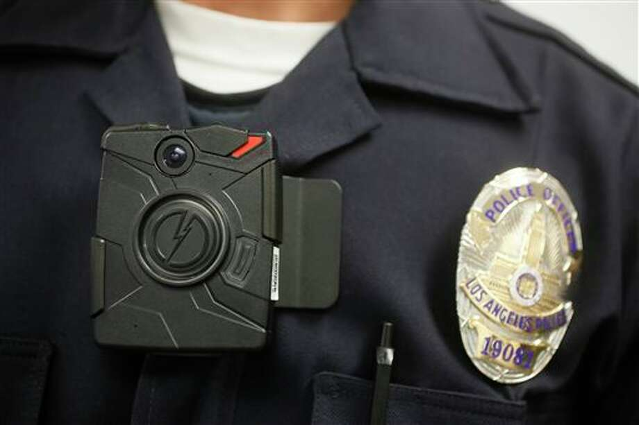 """FILE - In this Jan. 15, 2014 file photo, a Los Angeles Police officer wears an on-body camera during a demonstration for media in Los Angeles. The fatal police shooting of the unarmed black teenager in Ferguson, Mo. has prompted calls for more officers to wear so-called """"body cameras,"""" simple, lapel-mounted gadgets that record the interactions between the public and law enforcement. (AP Photo/Damian Dovarganes, File) Photo: THE ASSOCIATED PRESS / A2014"""