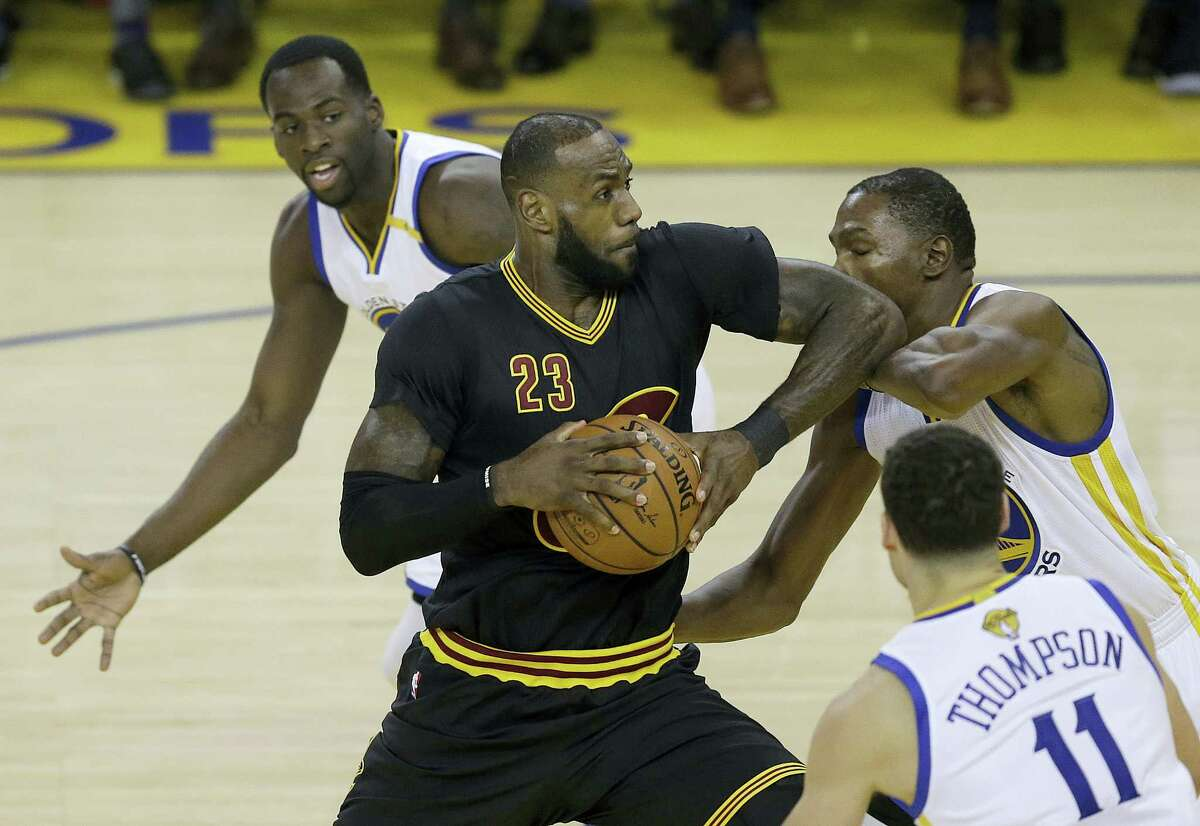 Cavaliers forward LeBron James (23) shoots between Warriors forward Draymond Green, top, guard Klay Thompson and forward Kevin Durant during Game 2 of the NBA Finals on Sunday.