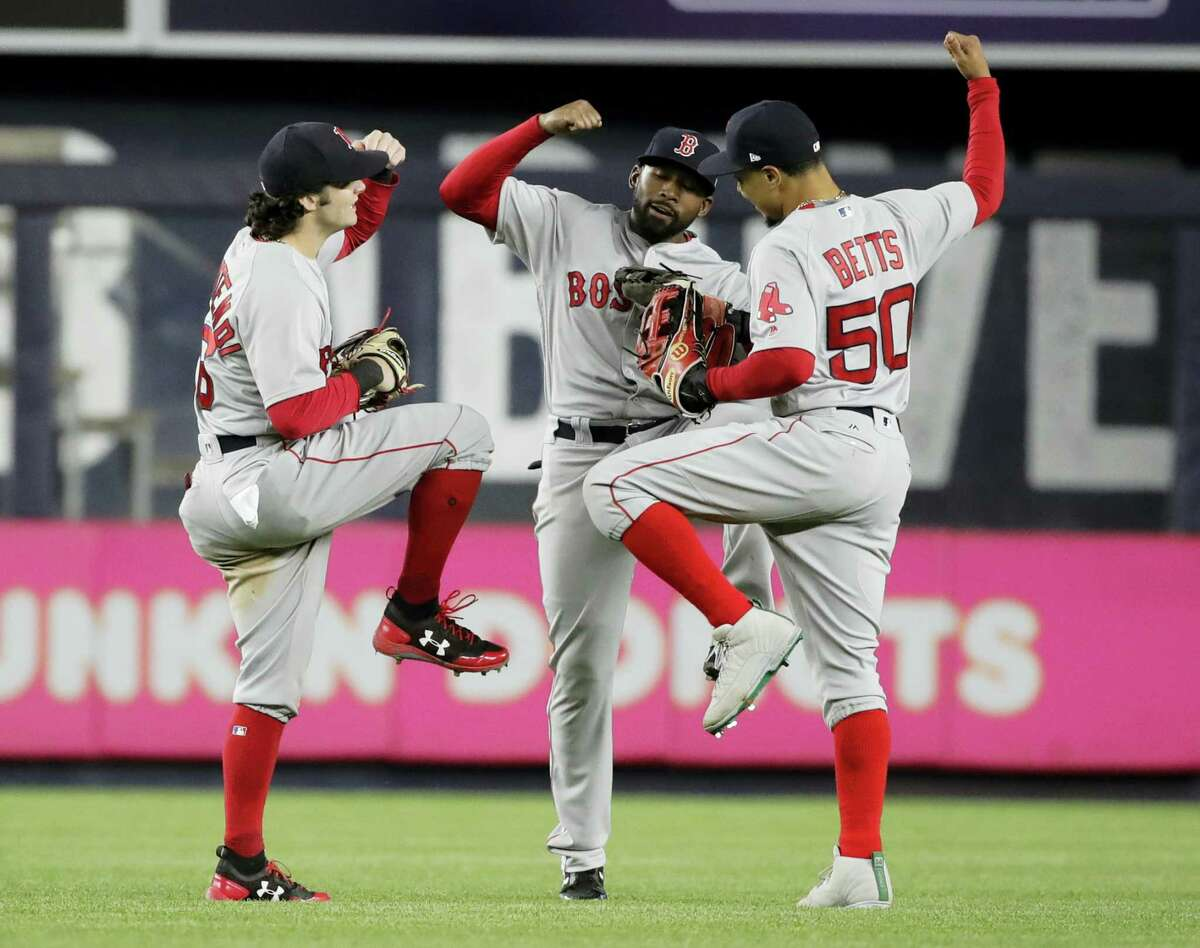 Red Sox outfielder Andrew Benintendi, left, celebrates with teammates Mookie Betts, right, and Jackie Bradley Jr. after Tuesday's win over the Yankees.