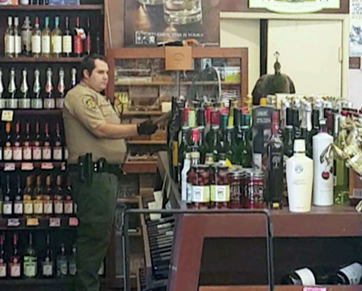 In this Monday, June 5, 2017 image made from cellphone video provided by Rani Ghanem, bottles tumble as an animal control officer attempts to net a female peacock that wound up inside the Royal Oaks Liquor Store in Arcadia, Calif. Store manager and college senior Rani Ghanem says he tried to guide the sharp-clawed bird outside but that she spooked, at one point flying directly toward him and then up onto a top shelf of the store.