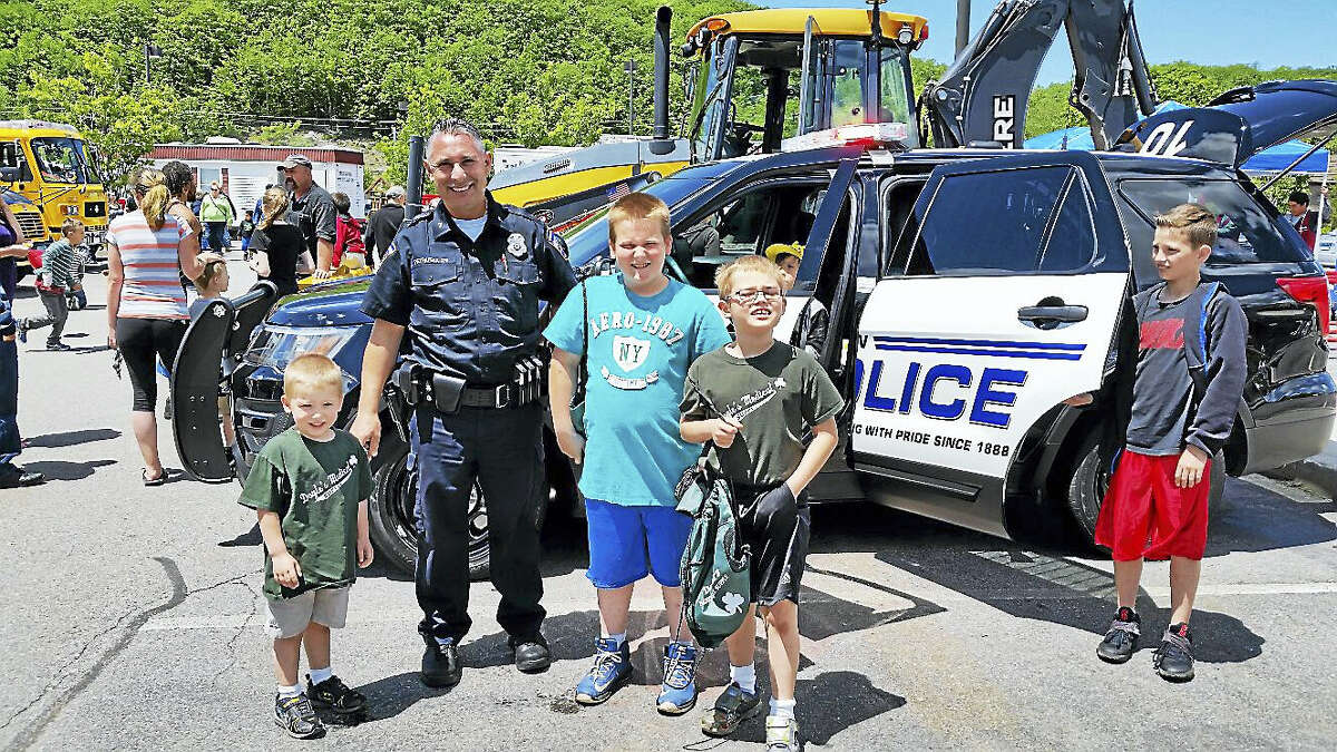 """Torrington Police Officer Tony Pietrafesa showed children """"Chase,"""" a police van, during the eighth annual """"Touch a Truck"""" event in Torrington Saturday."""