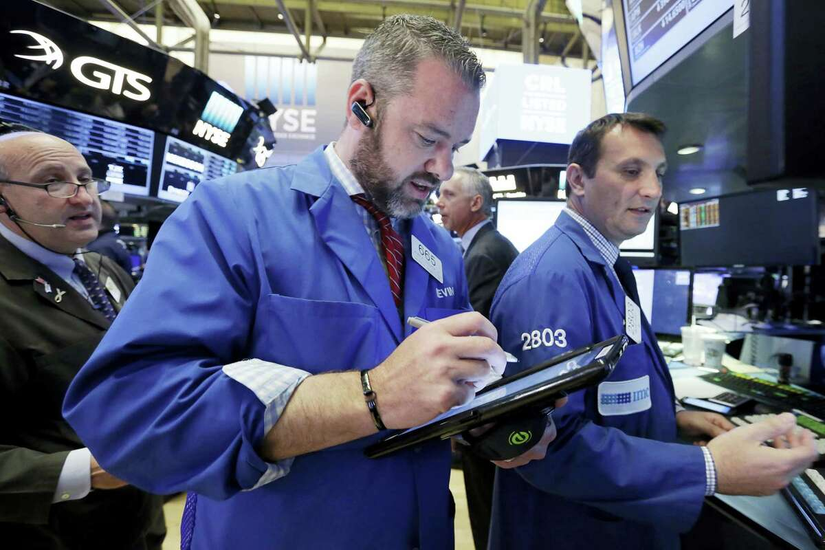 Trader Kevin Lodewick, center, works on the floor of the New York Stock Exchange.