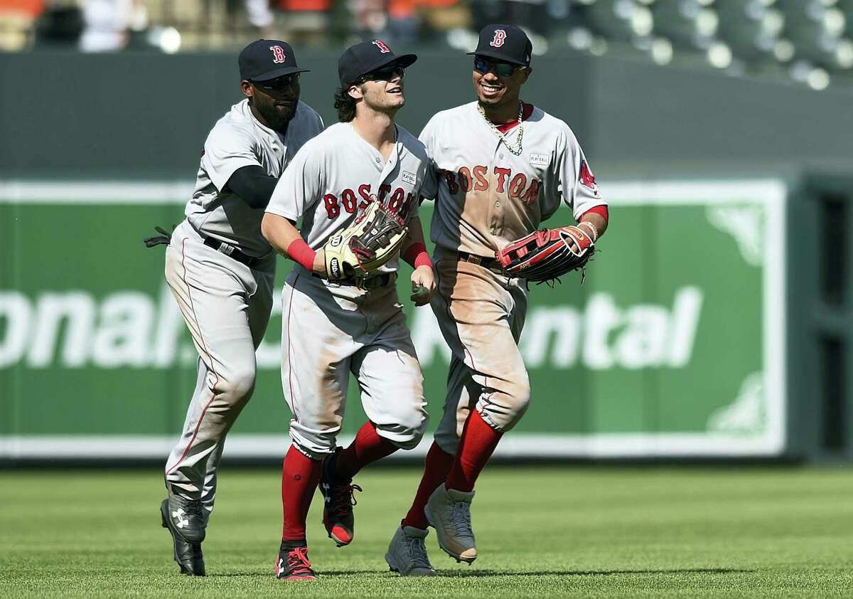 Red Sox outfielders, from left to right, Jackie Bradley Jr. Andrew Benintendi and Mookie Betts react after defeating the Orioles.
