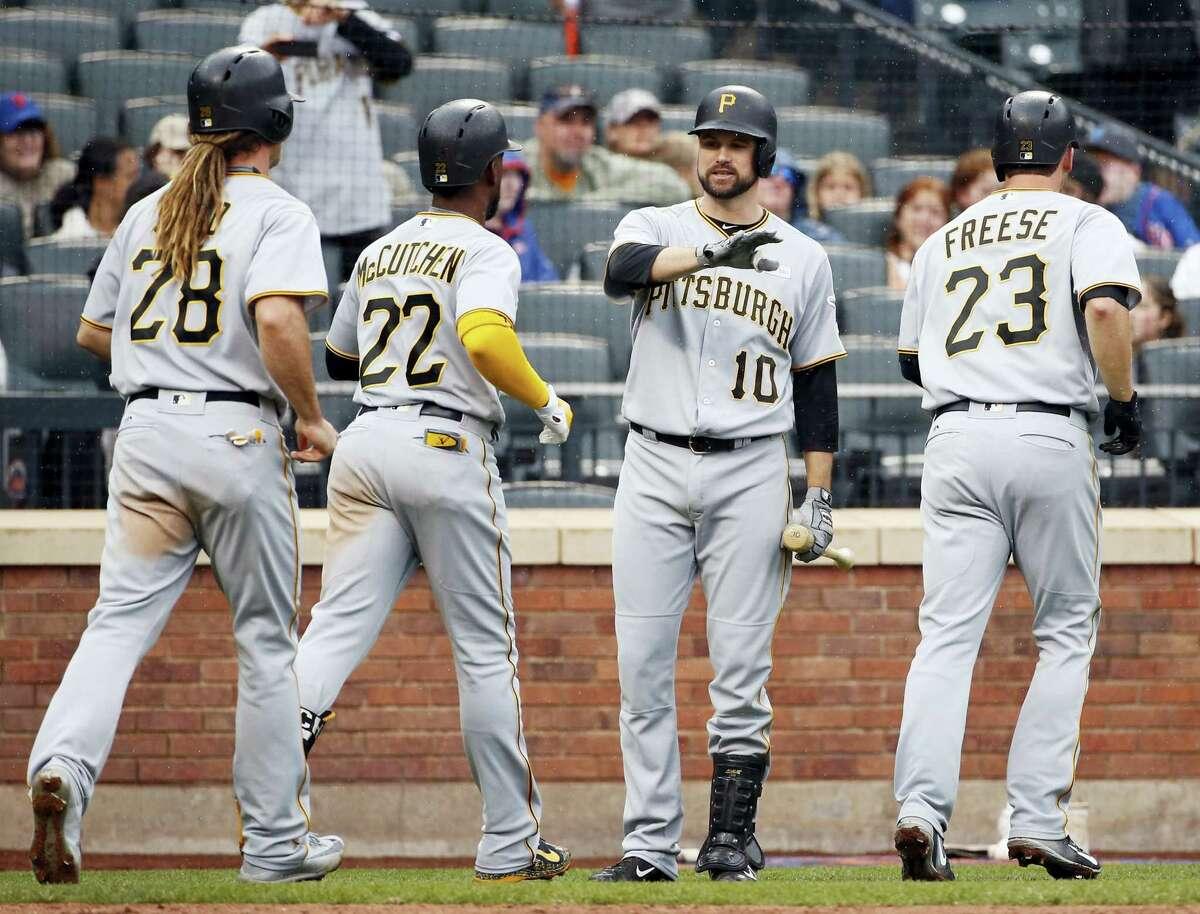 Pittsburgh Pirates Jordy Mercer, right, congratulates the Pirates' John Jaso, (28), Andrew McCutchen (22), and the Pirates' David Freese (23) after McCutchen hit a ninth-inning, three-run, home run.