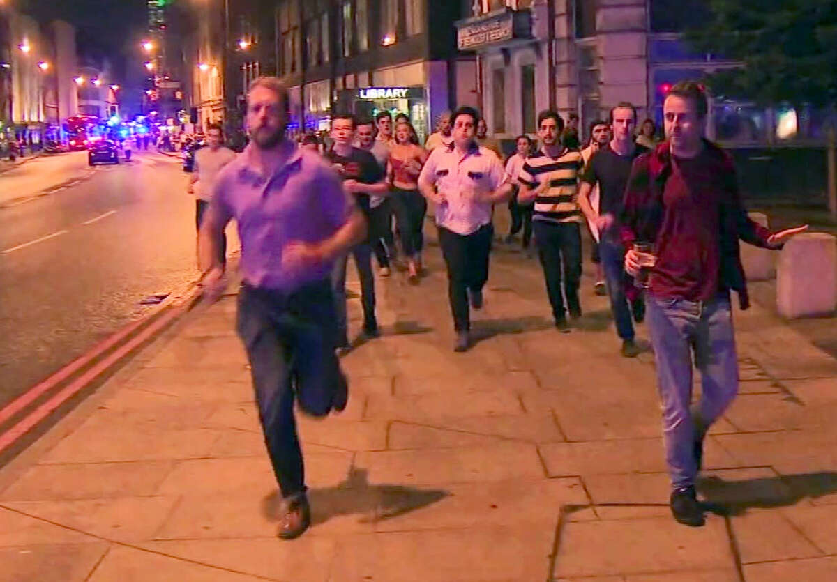 In this image taken from video footage, people run from the scene of attack, alongside a man strolling holding a pint of beer, right, in London, late Saturday, June 3, 2017. People in the U.K. have responded to the deadly London Bridge attack with sorrow and distinctly British humor, hailing a man pictured walking away from the mayhem holding a pint of beer as a tongue-in-cheek symbol of defiance. (Sky news via AP)