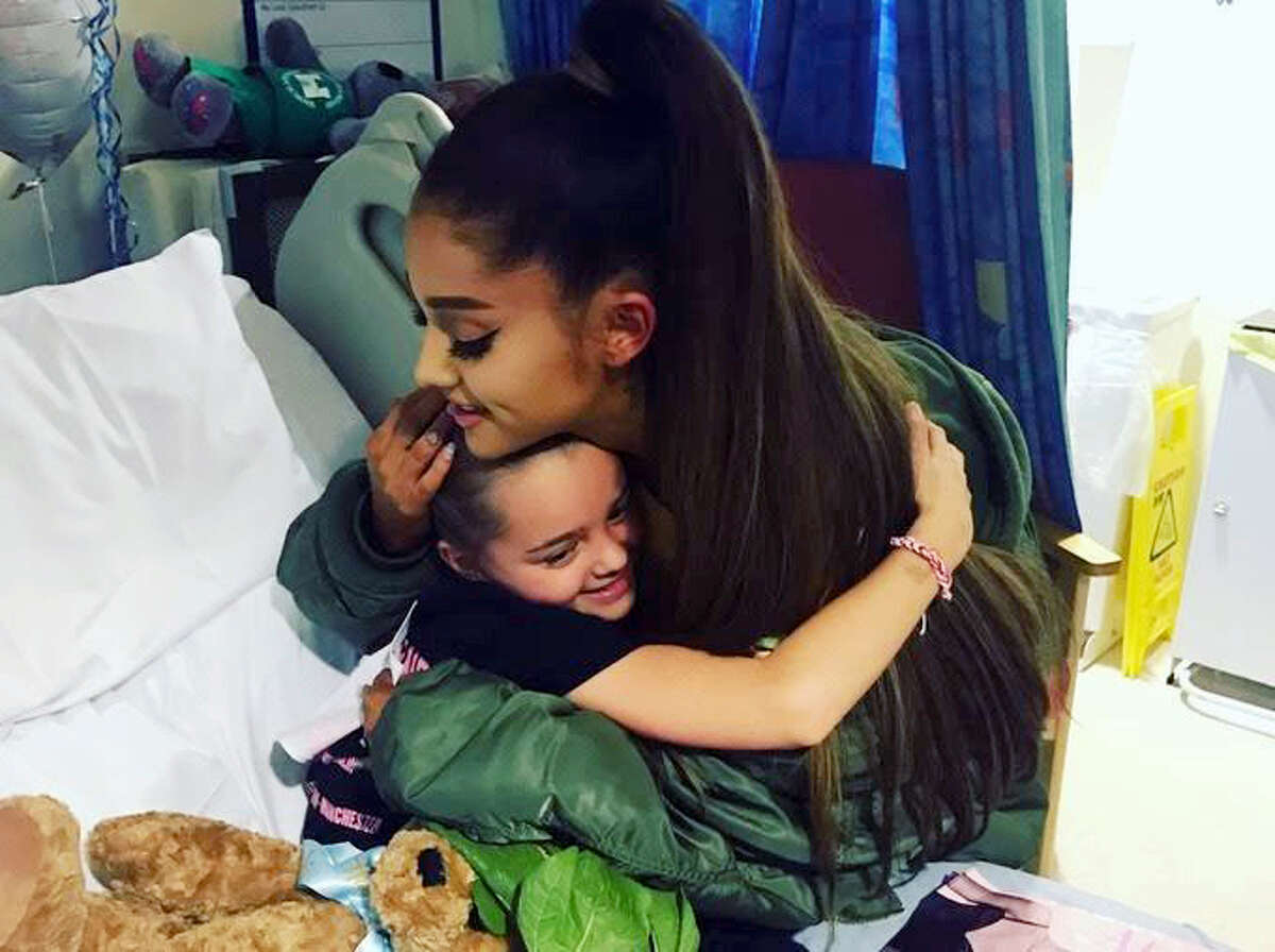 In this photo taken June 2, 2017 provided by the Manchester Evening News, victim of the Manchester concert blast Lily Harrison hugs singer Ariana Grande during her visit to the Royal Manchester Children's Hospital, in Manchester, England. Grande surprised young fans injured in the Manchester Arena attack, hugging the thrilled little girls in their hospital beds as they recovered from injuries sustained in the May 22 suicide bombing.