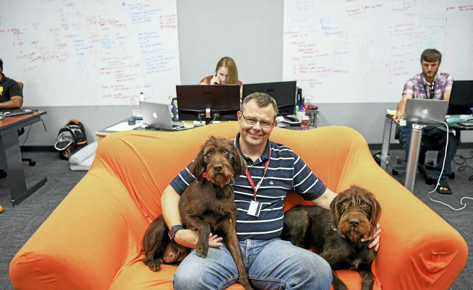 Mark Olcott, with his dogs Annie, left, and Surrey in Columbia, Md., is the co-founder of VitusVet, an app company that is building a computerized clearinghouse for animal-health-care records. Photo: Jonathan Newton — The Associated Pres  / The Washington Post