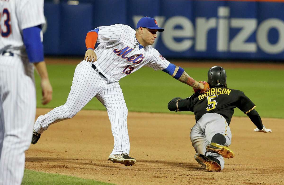 New York Mets shortstop Asdrubal Cabrera tags out Pittsburgh Pirates' Josh Harrison in a rundown during the fifth inning of the Pirates' 12-7 win Friday night.