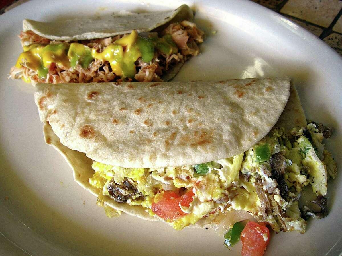 Machacado taco on a handmade flour tortilla, foreground, and a pollo guisado taco on handmade corn from Las Pichanchas Cafe.