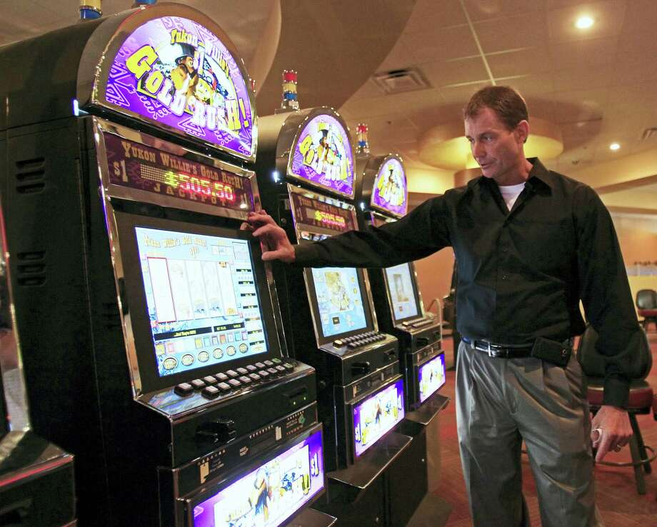 """Bobby Geiger of Oaklawn Racing and Gaming explains how wagers are placed on a """"Yukon Willie's Gold Rush!"""" game in the instant racing area at Kentucky Downs in Franklin, Ky. Photo: The Associated Press File Photo  / AP2011"""