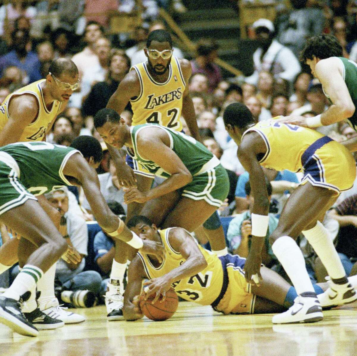The Lakers' Magic Johnson scrambles for the ball on the floor during an NBA finals in 1987.