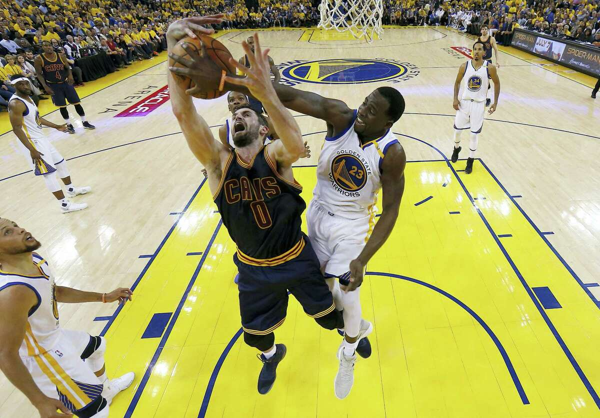 Warriors forward Draymond Green, right, defends a shot by the Cavaliers' Kevin Love during the first half of Game 1 of the NBA Finals in Oakland, Calif., on Thursday.