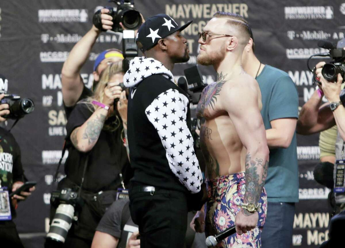 Floyd Mayweather Jr., left, and Conor McGregor, of Ireland, face each other for photos during a news conference in New York.