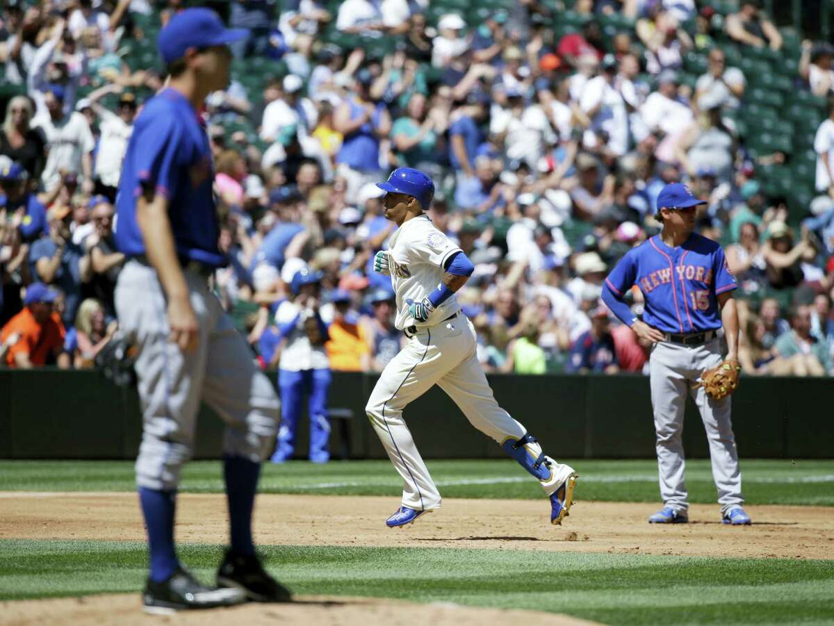 The Mariners' Leonys Martin, center, rounds the bases as Mets starting pitcher Seth Lugo looks on on Sunday.