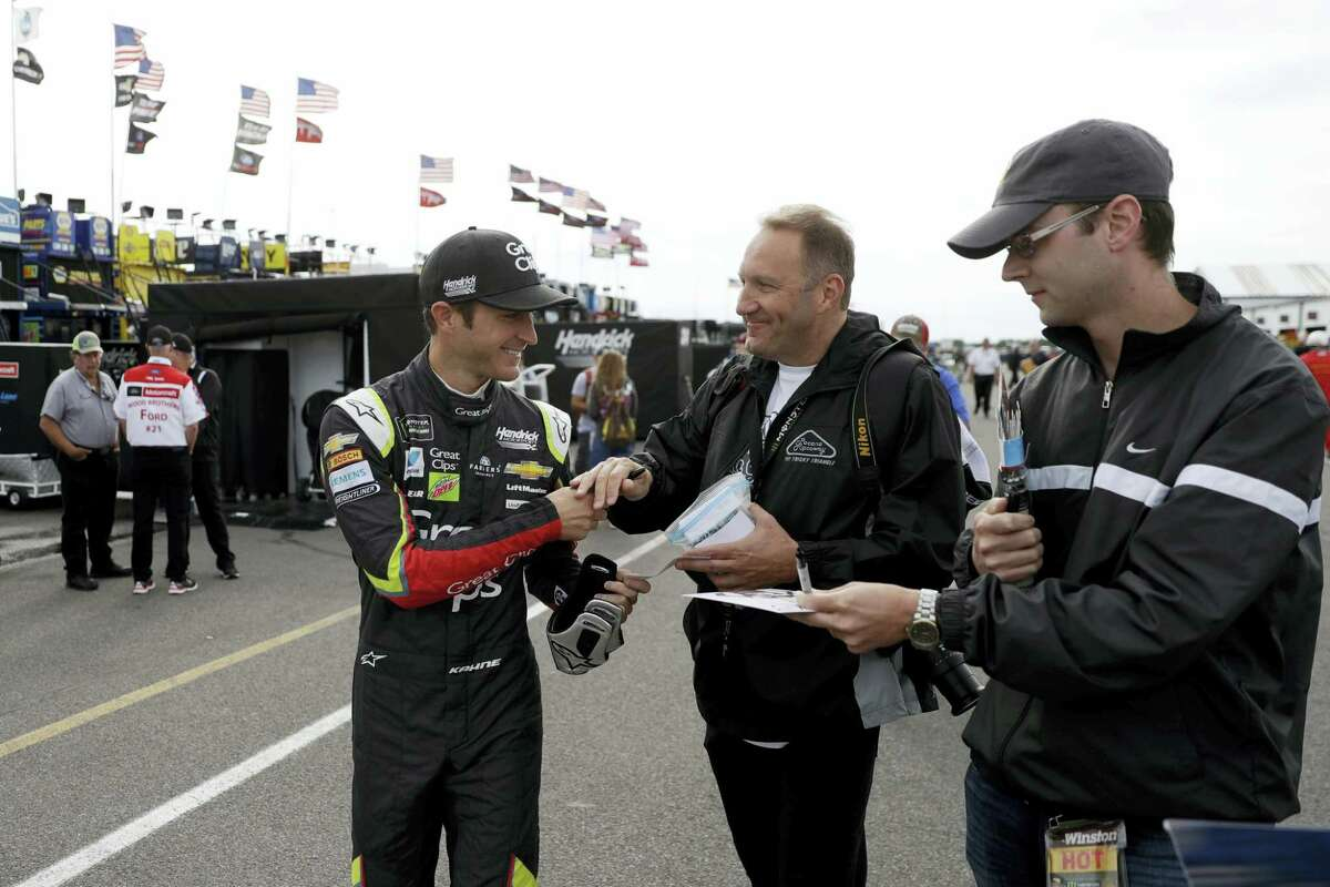 Kasey Kahne signs autographs for fans before a practice session in Long Pond, Pa.