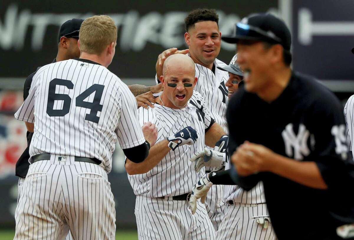 The Yankees' Brett Gardner, center, is mobbed by teammates after driving in Jacoby Ellsbury for the wining run against the Rays on Saturday in New York.