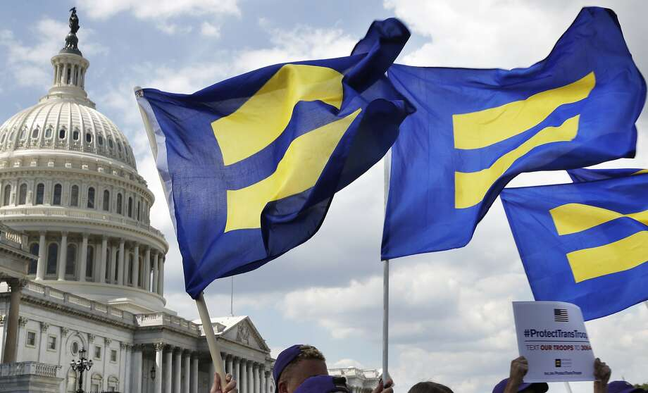 "In this July 26, 2017 file photo, people with the Human Rights Campaign hold up ""equality flags"" during an event on Capitol Hill in Washington, in support of transgender members of the military. Photo: Jacquelyn Martin, Associated Press"