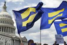 """FILE - In this July 26, 2017 file photo, people with the Human Rights Campaign hold up """"equality flags"""" during an event on Capitol Hill in Washington, in support of transgender members of the military. Officials say the Pentagon expects soon to ban transgender individuals from joining the military and to consider circumstances in which some currently serving transgender troops could remain in uniform.  (AP Photo/Jacquelyn Martin)"""