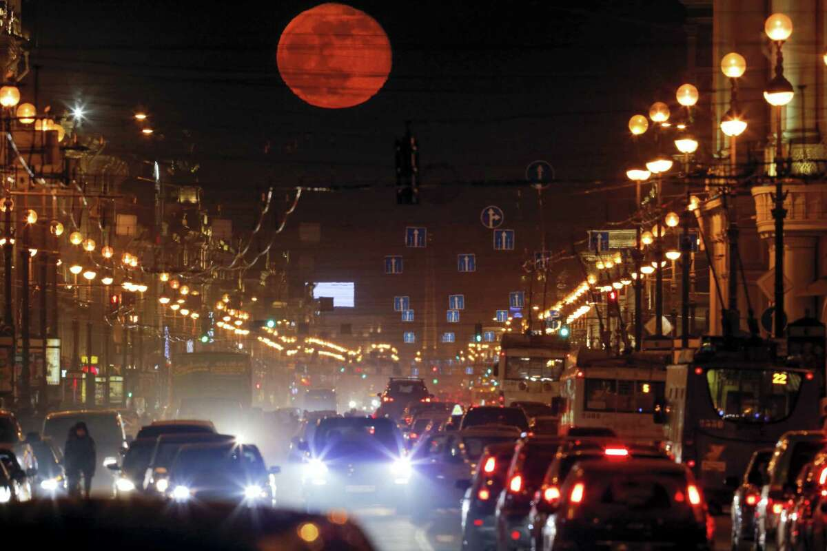 In this file photo taken on Thursday, March 24, 2016, the moon rises over Nevsky Prospect, Central Avenue, in St. Petersburg, Russia. The U.S. has orchestrated the arrest of five alleged Russian cybercriminals across Europe in the past nine months. The operations come at a fraught moment in relations between Russia and the U.S., where politicians are grappling with the allegation that Kremlin hackers intervened in the 2016 election.