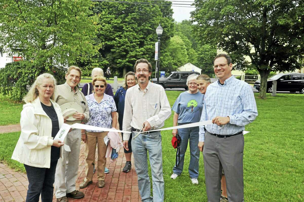 Members of Winsted Trails and residents took part in a ribbon-cutting and dedication for the City Walk, a trail running through downtown Winsted. In the center of the group is Winsted Trails member Ric Nalette.