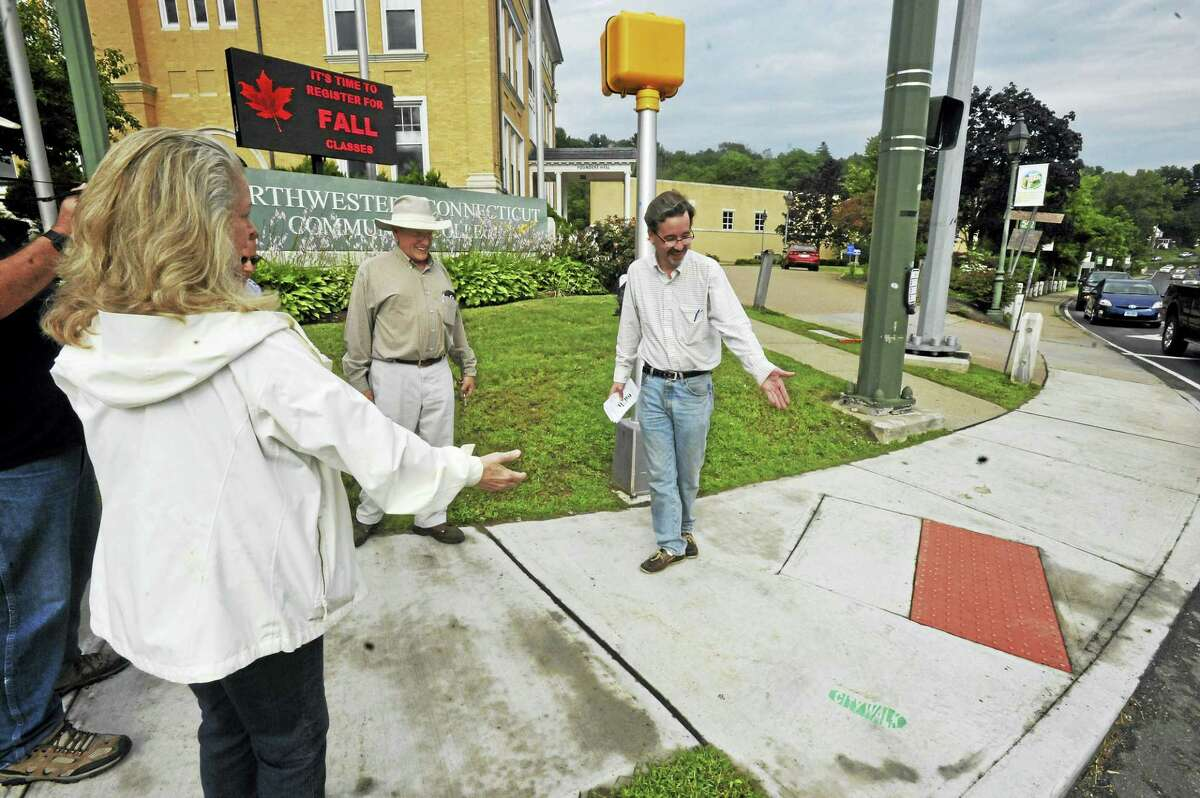 Winsted Trails members including Ric Nalette, right, point to a small green footprint on the pavement that indicates the start of the City Walk trail.