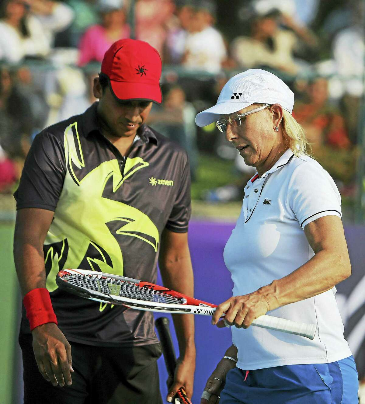 Tennis legend Martina Navratilova, right, speaks with her partner Mahesh Bhupathi during an exhibition mixed doubles match in India in 2015.