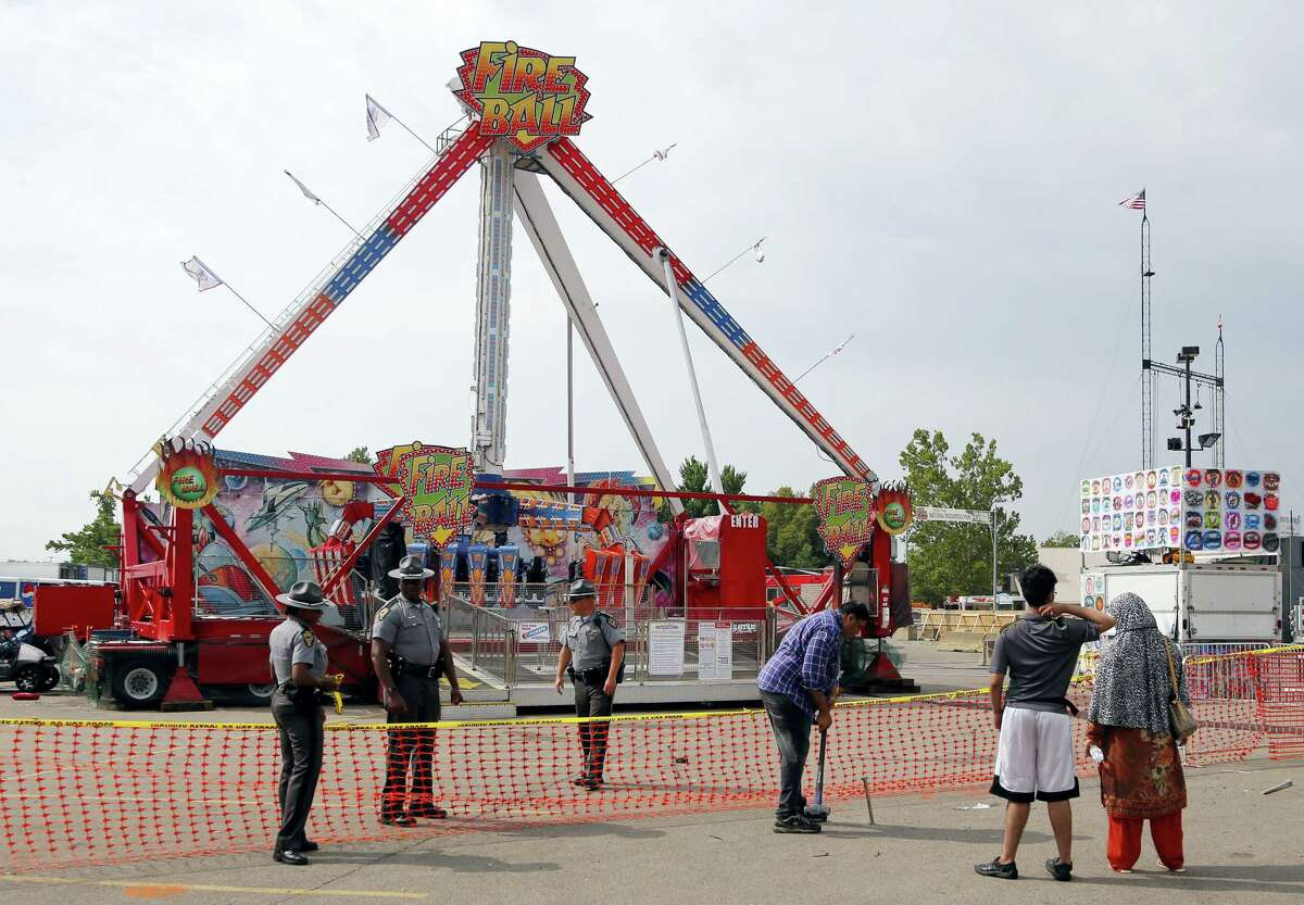 Passers by look at the fire ball ride as Ohio State Highway Patrol troopers stand guard at the Ohio State Fair Thursday, July 27, 2017, in Columbus, Ohio. The fair opened Thursday but its amusement rides remained closed one day after Tyler Jarrell, 18, was killed and seven other people were injured when the thrill ride broke apart and flung people into the air.