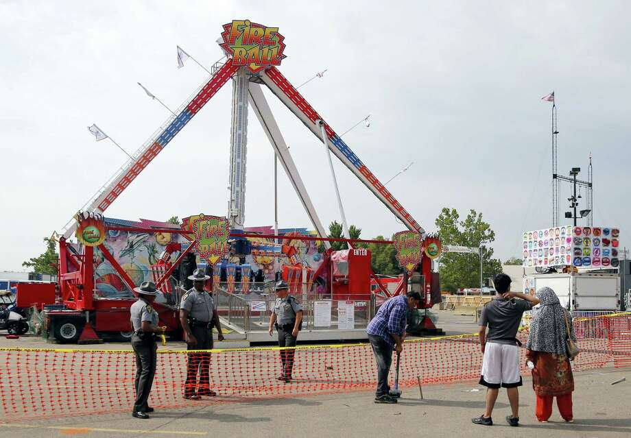 Passers by look at the fire ball ride as Ohio State Highway Patrol troopers stand guard at the Ohio State Fair Thursday, July 27, 2017, in Columbus, Ohio.   The fair opened Thursday but its amusement rides remained closed one day after Tyler Jarrell, 18, was killed and seven other people were injured when the thrill ride broke apart and flung people into the air. Photo: Jay LaPrete / AP Photo  / FR52593 AP