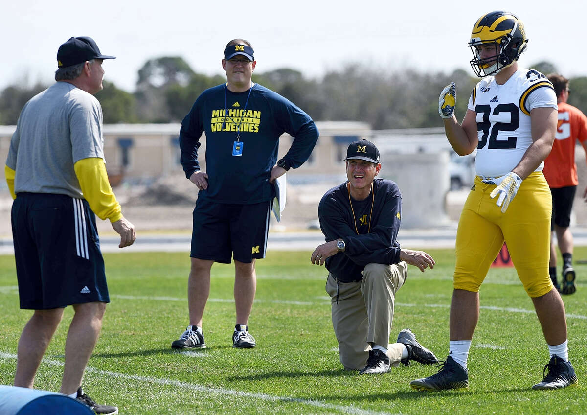 In this Feb. 29, 2016 photo, Michigan's head coach Jim Harbaugh, center right, watches defensive coordinator Don Brown, left, work with Cheyenn Robertson during NCAA college football practice in Bradenton, Fla. The two-a-day football practices that coaches once used to toughen up their teams and cram for the start of the season are going the way of tear-away jerseys and the wishbone formation.