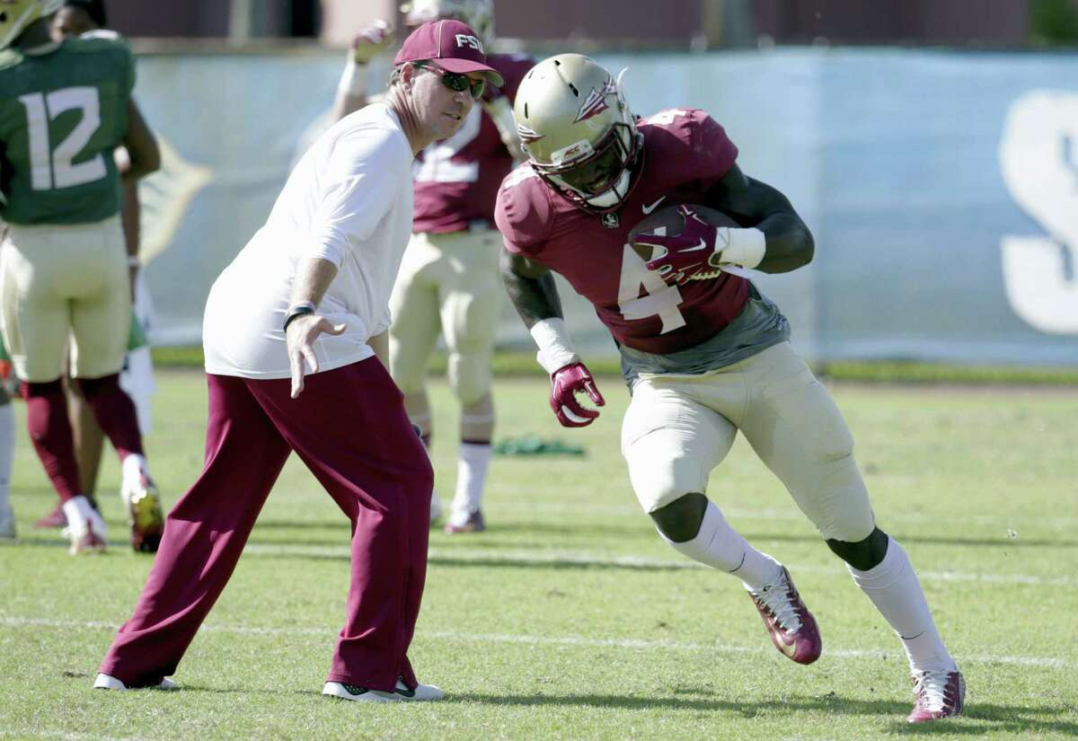 In this Dec. 27, 2016 photo, Florida State running back Dalvin Cook (4) runs as head coach Jimbo Fisher looks on during NCAA college football practice in Fort Lauderdale, Fla. The two-a-day football practices that coaches once used to toughen up their teams and cram for the start of the season are going the way of tear-away jerseys and the wishbone formation.