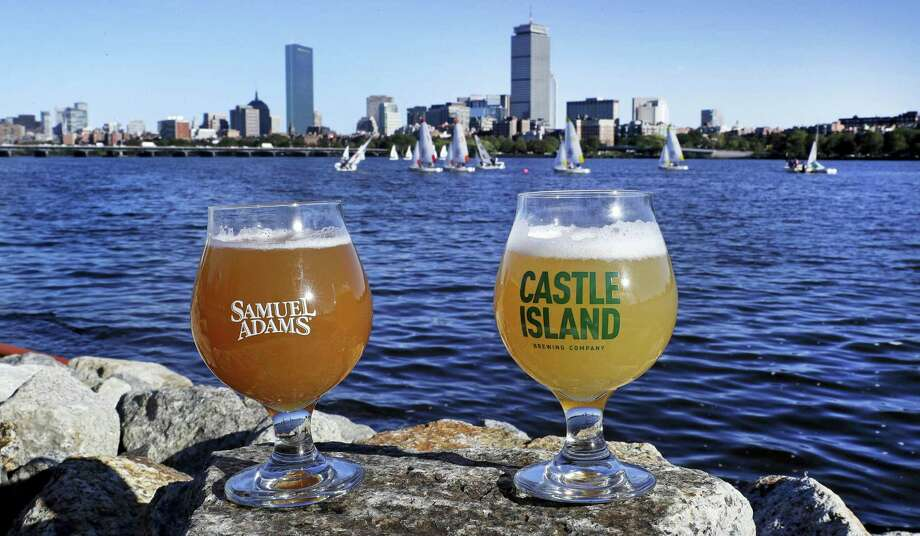 """A glass of Samuel Adams Boston Beer Company """"80-Miles of Helles"""" beer, left, and a glass of Castle Island Brewing Company """"Chuck"""" dry hopped cream ale rest on a rock along the bank of the Charles River. Photo: AP Photo — Charles Krupa/file  / Copyright 2016 The Associated Press. All rights reserved."""