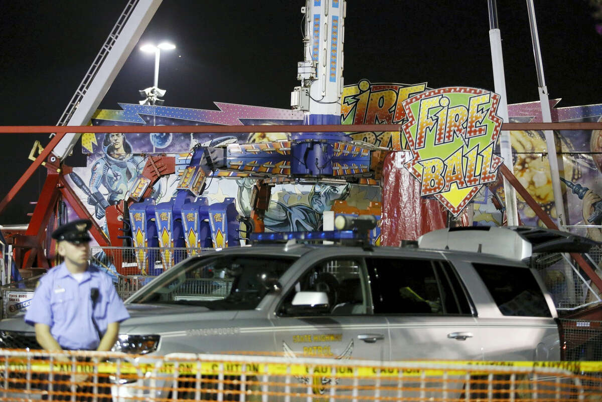 Authorities stand near the Fire Ball amusement ride after the ride malfunctioned injuring several at the Ohio State Fair, Wednesday, July 26, 2017, in Columbus, Ohio. Some of the victims were thrown from the ride when it malfunctioned Wednesday night, said Columbus Fire Battalion Chief Steve Martin. (Barbara J. Perenic/The Columbus Dispatch via AP)