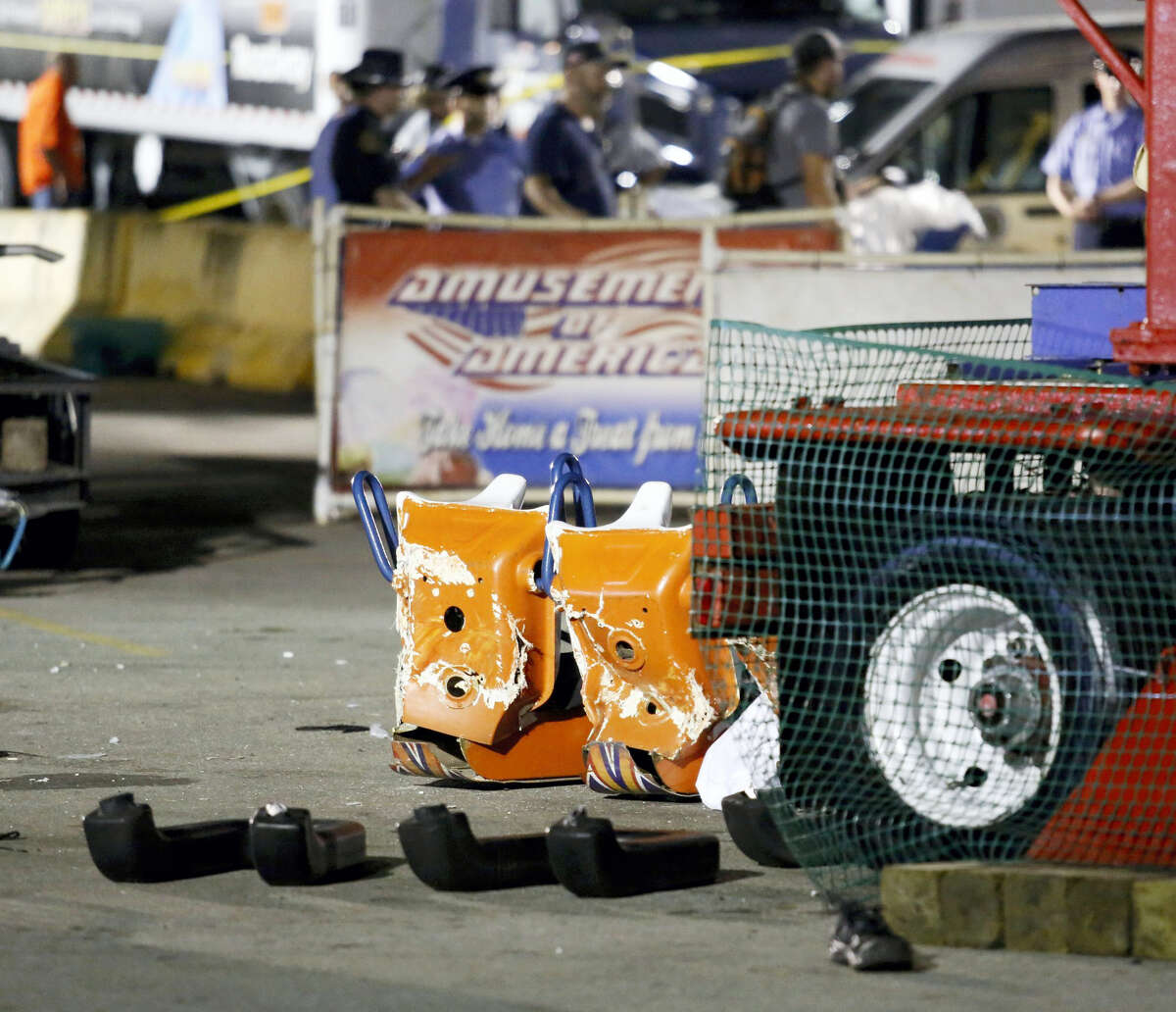 Authorities stand near damaged chairs of the Fire Ball amusement ride after the ride malfunctioned injuring several at the Ohio State Fair, Wednesday, July 26, 2017, in Columbus, Ohio. Some of the victims were thrown from the ride when it malfunctioned Wednesday night, said Columbus Fire Battalion Chief Steve Martin. (Barbara J. Perenic/The Columbus Dispatch via AP)