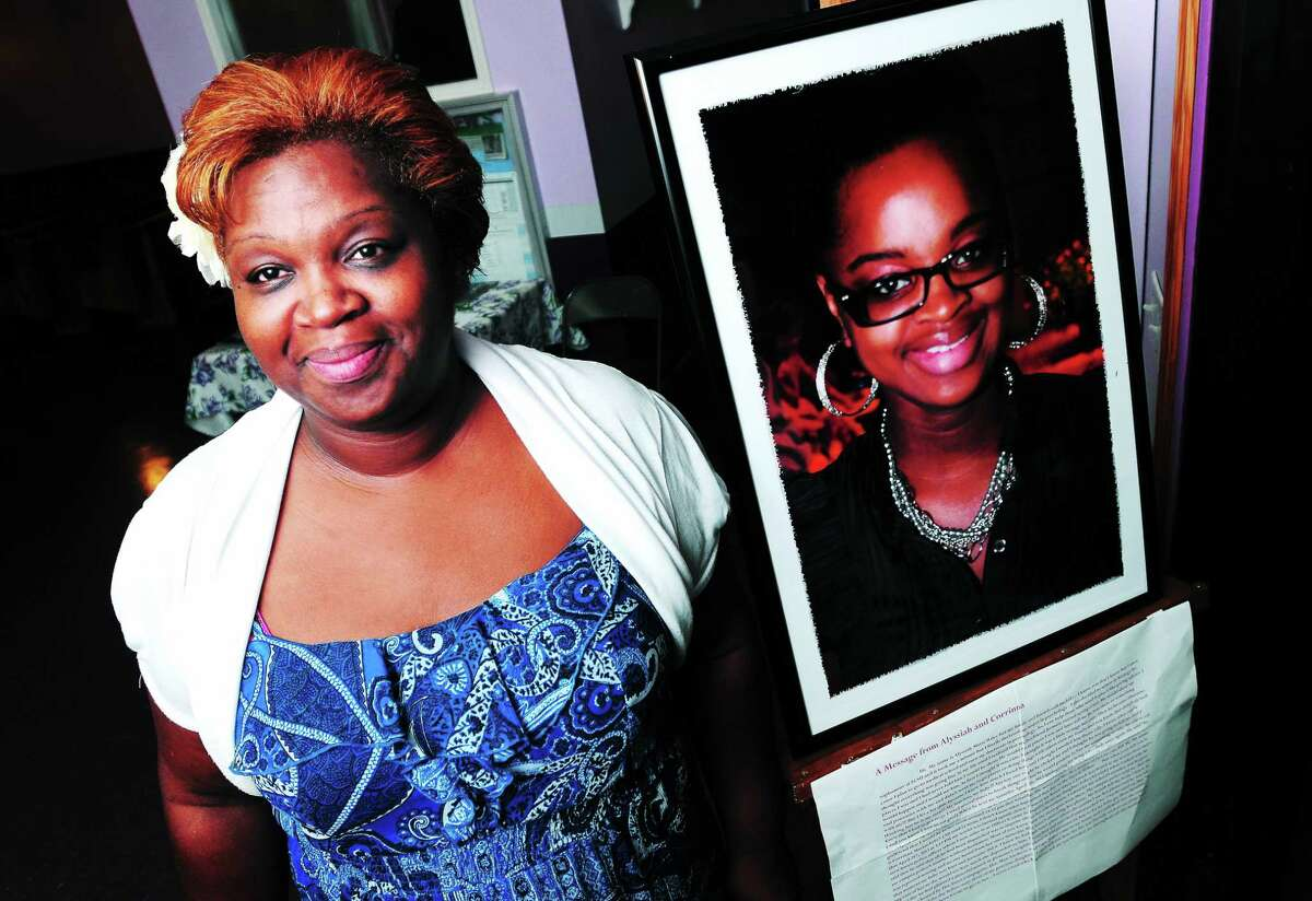 Corrinna Martin stands next to a photograph of her slain daughter, Alyssiah Wiley, at Morning Star Deliverance Church in New Haven during a gospel fundraiser for M.O.V.E., or Mother's of Victim's Equality in 2013.