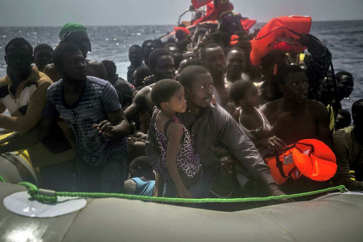 Migrants wait to be rescued by aid workers of Spanish NGO Proactiva Open Arms in the Mediterranean Sea, about 15 miles north of Sabratha, Libya on Tuesday, July 25, 2017.