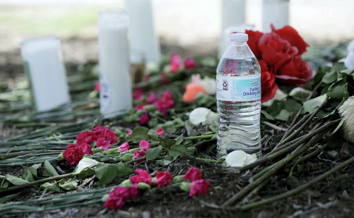 A bottle of water, flowers, candles, and stuffed animals help form a makeshift memorial in the parking lot of a Walmart store near the site where authorities Sunday discovered a tractor-trailer packed with immigrants outside a Walmart in San Antonio, Monday, July 24, 2017. Several people died and others hospitalized after being crammed into a sweltering tractor-trailer in the midsummer Texas heat, according to authorities in what they described as an immigrant-smuggling attempt gone wrong.