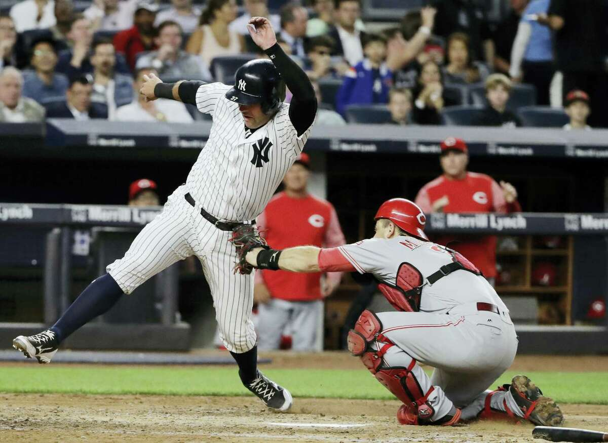 Cincinnati Reds catcher Devin Mesoraco tags out New York Yankees' Austin Romine, left, at home plate during the fifth inning of the Yankees' 4-2 win.