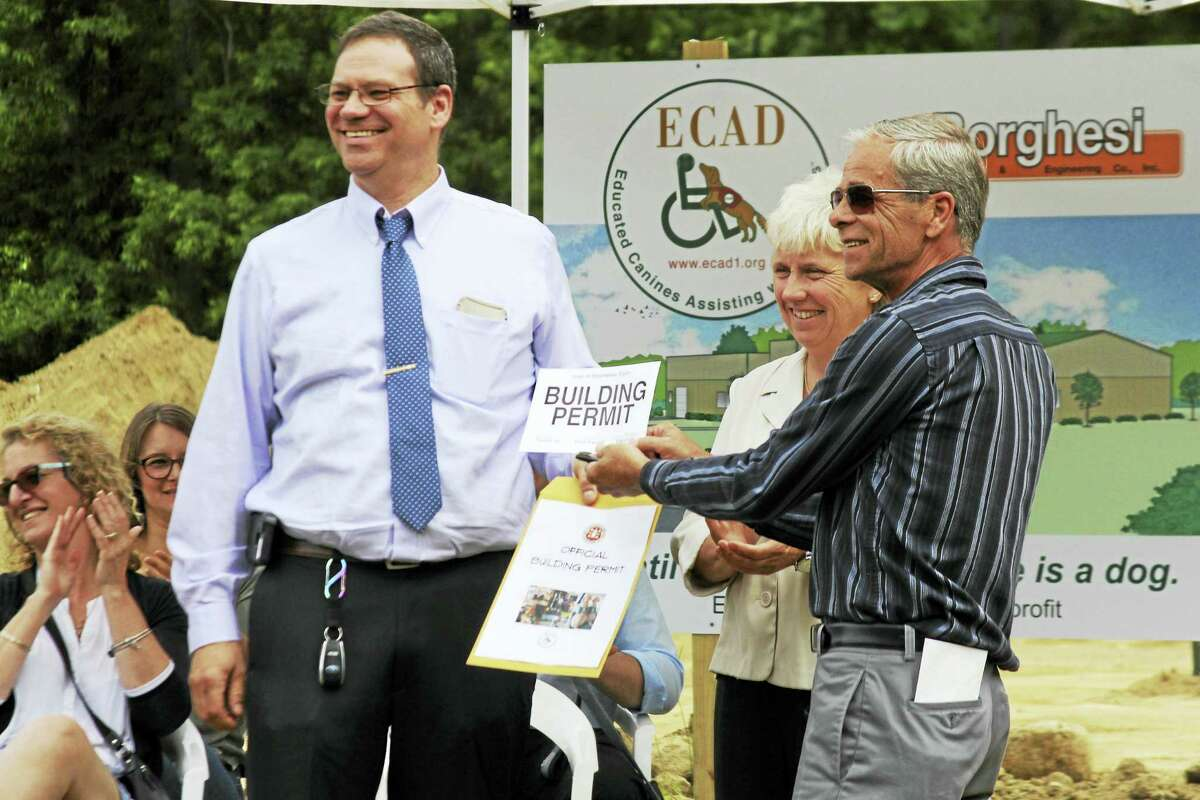Steven Sadlowski, director of Planning and Community Development, joins Winsted Mayor Althea Candy Perez in presenting the official building permit to ECAD co-founder, Dale Picard, during groundbreaking ceremonies for ECAD's new Canine Education and Wellness Center.