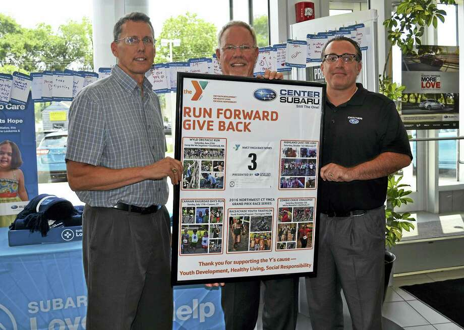 "Photo Caption:On Friday, July 21, Northwest CT YMCA CEO Greg Brisco, left, presented Center Subaru Owner Phil Porter, middle, and General Manager Andy Maiolo with a special framed ""Thank You"" poster to honor the dealership's continued support as the Presenting Sponsor of the Y's Grand Prix Race Series. 2016 marked the third consecutive year Center Subaru was the main sponsor of the 4-event Race Series. The dealership is sponsoring the Race Series once again in 2017, with the next run being the Highland Lake 10K in Winsted on Oct. 7. Photo: Digital First Media"