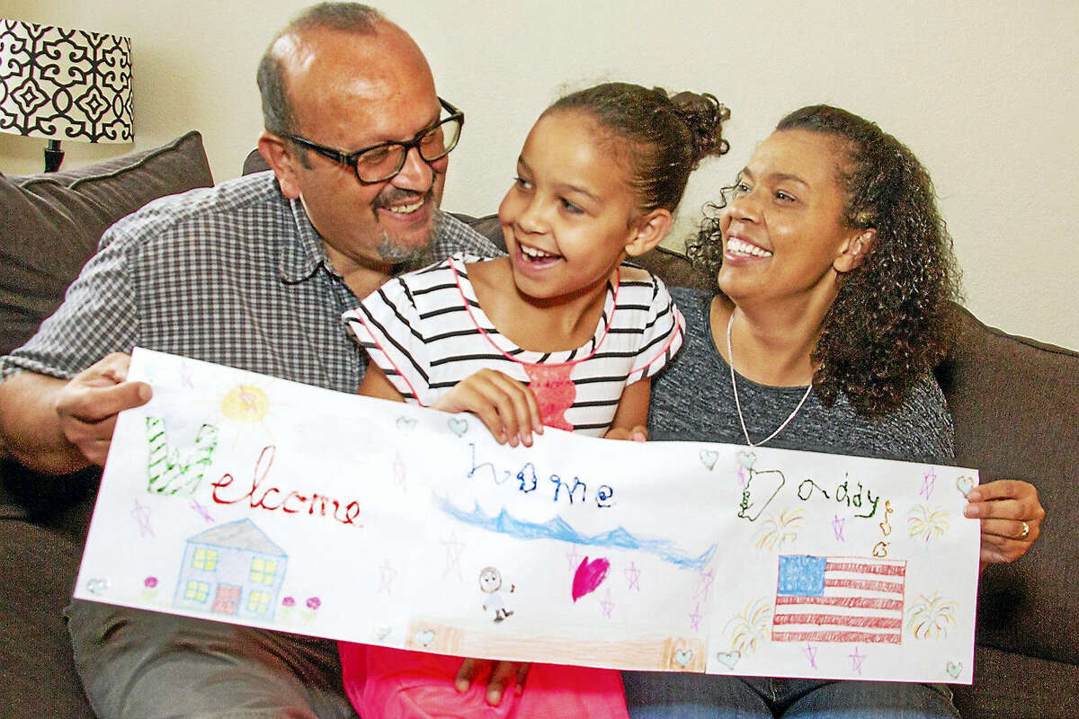 Blair Giammarco, 8, shows the welcome home banner she made for her father's homecoming as she sits in the family living room with father, Arnold and mother, Sharon.